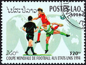 """LAOS - CIRCA 1994: A stamp printed in Laos from the """"World Cup Football Championship, U.S.A."""" 4th issue shows soccer players on world map, circa 1994. — Stock Photo"""