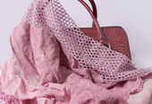 Pink scarf thrown over a leather bag — Stock Photo
