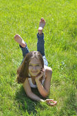 Girl lying on green grass and smiling — Stock Photo