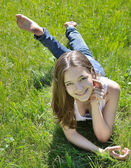 Smiling young girl in the summer grass — Стоковое фото