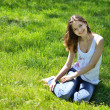 Smiling girl sitting on the green grass — Stock Photo