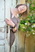 Kvinna som tittar ut genom dörren — Stockfoto