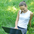 Stock Photo: Young girl with computer on grass