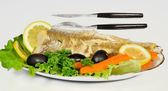 Baked fish with lemon, olives and vegetables on the plate — Stock Photo