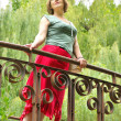 Woman in a red skirt on a bridge — Stock Photo