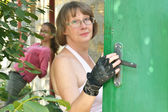 Woman opens the door of her home — ストック写真