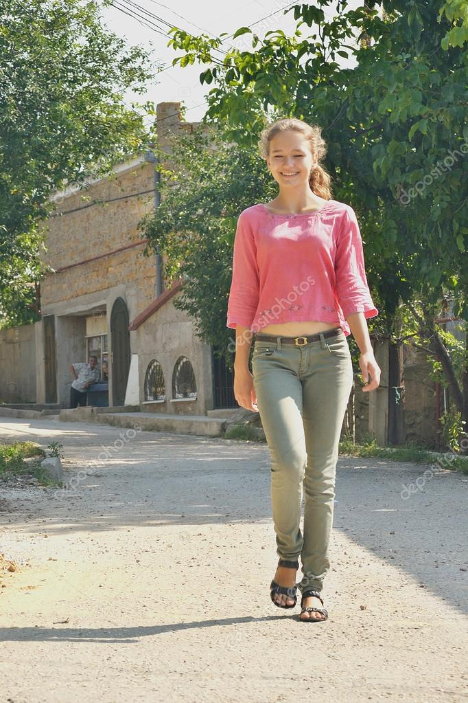 Young girl walking down the street of the village stock image
