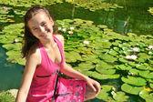 Jovem garota em um vestido vermelho, perto da lagoa — Foto Stock
