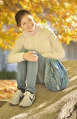 Young girl sitting on the parapet of the stairs bright autumn da — Stock Photo
