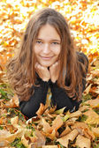 Young girl lying on autumn leaves — Stock Photo