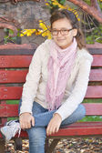 Smiling girl in jeans sitting on a park bench — ストック写真