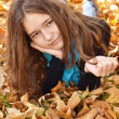 Young girl and fallen autumn leaves — Stock Photo
