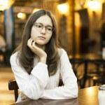 jeune fille attend quelqu'un à une table dans un café — Photo #38855369