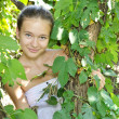 Young girl in the leaves of the tree in summer — Stock Photo