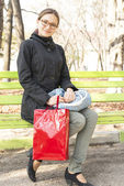 Girl sitting on a bench with a gift bag — ストック写真