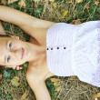 Girl in sundress lying on grass — Stock Photo #39311685