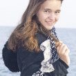 Stock Photo: Portrait of a smiling young girl on a background of the sea