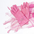Leather gloves and a pink and white scarf — Stock Photo