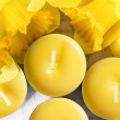 Yellow candles and yellow daffodils — Stock Photo