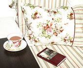 Sofa with a cup of tea and a book — Stock Photo