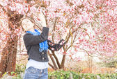 Young girl in jeans and a blooming garden — Foto Stock