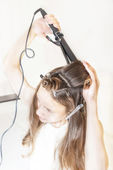 Young girl doing a hair using curling — Stock Photo
