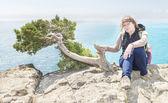 Turystyczne kobieta siedzi na klifie nad morzem — Zdjęcie stockowe