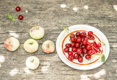 Broken apples and a plate with cherries on old wooden table — Stock Photo