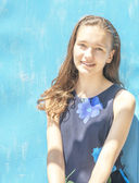 Young girl with curly hair on blue background wall — Stock Photo