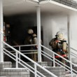 Firefighters team at burning house — Stock Photo #13180680