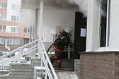 Firefighter enters to smoking buiding — Stock Photo