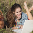 Young woman lying in field and smiling at white laptop — Stock Photo