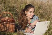 白いラップトップにフィールドに横になっている若い女性 — ストック写真