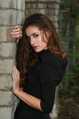 Beautiful girl in black dress standing at grey brick wall — Стоковое фото