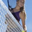 Beautiful girl tennis player standing at net — Stock Photo