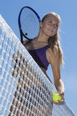 Beautiful girl tennis player standing at net — Stock Photo