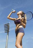Tenis oyuncu raket ve içme suyu tutar — Stok fotoğraf