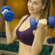 Beautiful fitness woman practicing with dumbbells — Stock Photo