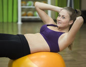 Young woman working out on fitness ball — Stock Photo