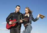 Young couple playing acoustic guitar and dancing — Stock Photo