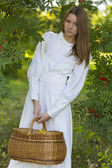 Beautiful girl in white dress holding a basket — Stock Photo