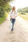 A woman walks down the road with a bag in his hand — Stock Photo