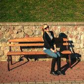 Kobieta siedzi na ławce w parku — Zdjęcie stockowe