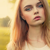 Beautiful blonde close-up portrait over bright daylight background in park — Stock Photo