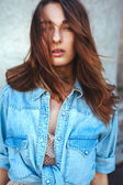 Portrait of an attractive stylish young brunette woman in blue jeans jacket — Stock Photo
