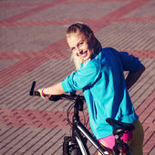 Girl with bicycle smiling and looking in camera — Stockfoto