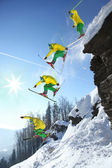 Skier jumping against blue sky from the rock — Stock Photo