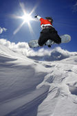 Snowboarder jumping against blue sky — Stock Photo