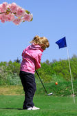 Little girl playing golf durimg spring time — Stock Photo