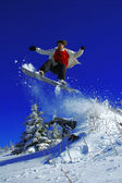 Snowboarders jumping against blue sky — ストック写真